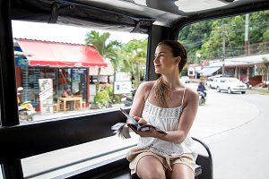 girl tourist in a Thai tuk Tuk taxi