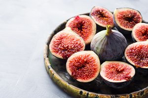 Dish of purple figs on gray background