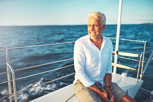 Smiling mature man sailing his boat alone on the ocean