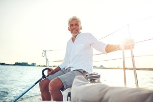 Smiling mature man sitting on the deck of a sailboat