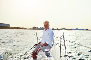Mature man sailing his yacht on the open water