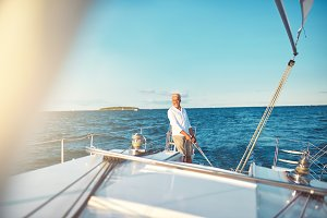 Mature man steering his sailboat on the open ocean