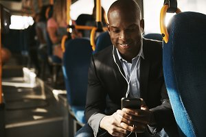 Smiling African businessman listening to music on his morning commute