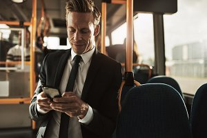 Smiling young businessman reading texts while standing on a bus