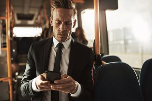 Young businessman standing on a bus sending text messsages