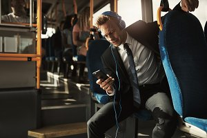 Smiling businessman riding a bus and listening to music