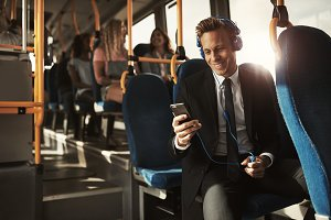 Smiling young businessman listening to music on his morning commute
