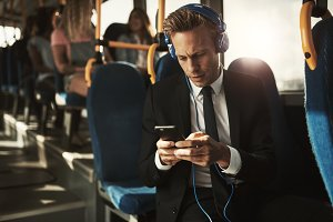 Businessman wearing headphones and reading text messages on a bus