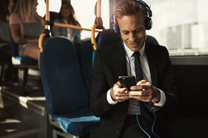 Smiling businessman wearing headphones and reading texts on a bus