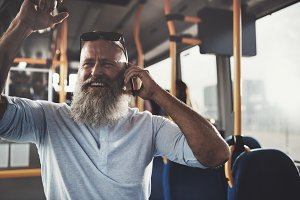 Smiling mature man talking on the phone on a bus