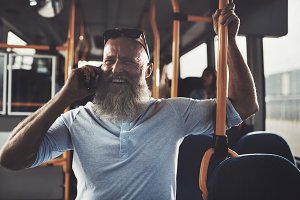 Smiling mature man standing a bus talking on his cellphone