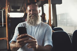 Smiling man with a beard reading texts on the bus