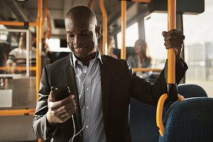Young African businessman standing on a bus listening to music