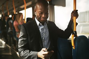 Smiling African businessman standing on a bus listening to music