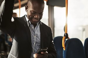 Smiling African businessman riding on a bus listening to music