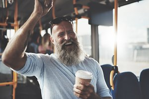 Bearded man standing on a bus drinking coffee and laughing