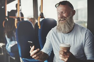 Bearded man laughing while using his cellphone on the bus
