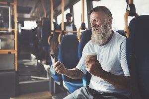 Mature man laughing while using his cellphone on the bus