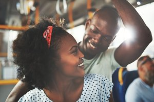 Affectionate young African couple standing together on a bus