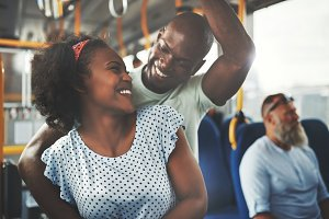 Smiling young African couple standing affectionately together on a bus
