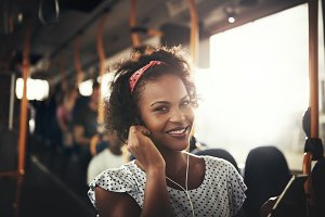 Smiling African woman standing on a bus listening to music