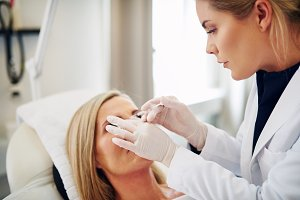 Doctor injecting botox into the forehead of a mature woman