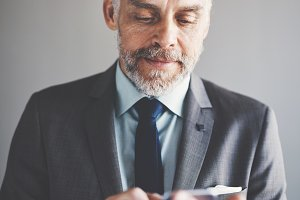 Focused mature businessman send texts on a cellphone