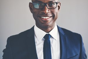 Smiling young African executive wearing a suit and glasses