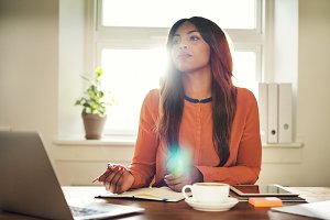 Young female entrepreneur thinking while working online at home