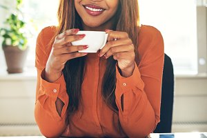Smiling young woman drinking coffee while working from home