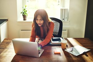 Young female entrepreneur working online at a desk at home