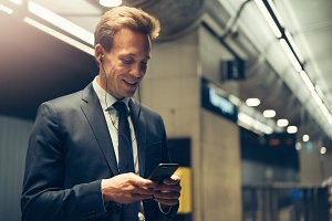 Smiling businessman standing in a subway station reading text messages