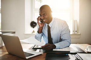 Young businessman sitting at work discussing paperwork over the phone