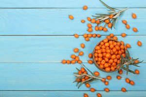 Sea buckthorn. Ripe fresh berries in bowl on blue wooden background with copy space for your text. Top view