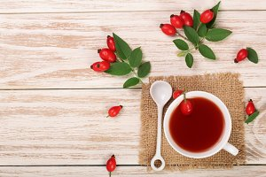 tea with rose hips and honey on a white wooden background with copy space for your text. Top view