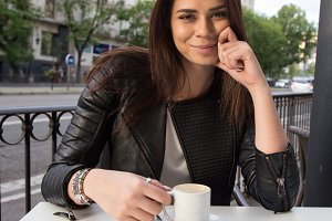 Girl drinking coffee in the street