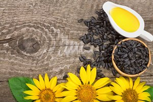 Sunflower oil, seeds and flower on wooden background with copy space for your text. Top view