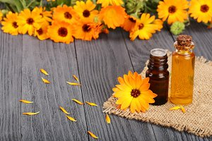 aromatherapy essential oil with fresh marigold flowers on old wooden background. Calendula oil