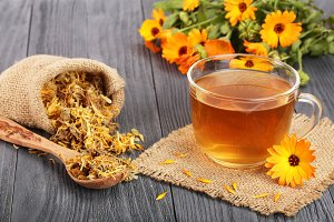 Calendula tea with fresh and dried flowers on black wooden background
