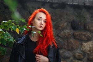 Portrait of beautiful redhead girl on dark wall outdoor. Unformal woman with vibrant colorful hairstyle standing among birch branches. Autumn.