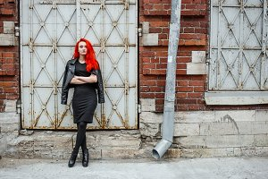 Redhead unformal girl standing near brick wall with metall doors. Urban street style