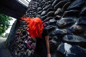 Red hair fluttering. Dark stone wall. Creepy horror image