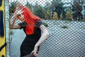 Fashionable redhead woman holding torn grid