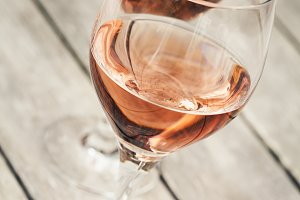 Two glasses of rose wine on wooden table, shallow DOF
