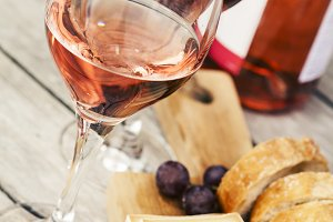 Two glasses of rose wine and board with fruits, bread and cheese on wooden table, shallow DOF