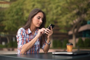 Attractive young woman reading a text message on her cell phone. Girl sitting outdoors using smartphone