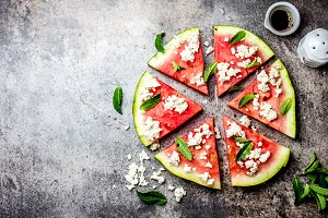 Fresh watermelon pizza salad with feta cheese, mint, salt and oil on stone background