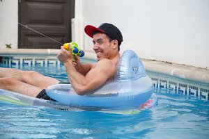 Cheerful man with water gun in pool