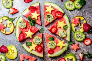 Fruit watermelon pizza with tropical fruits and berries - mango, tuna and mint on stone gray background. Pizza made of watermelon and fruits, top view