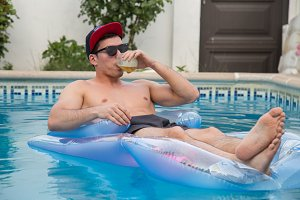 Strong man on an air bed in the pool